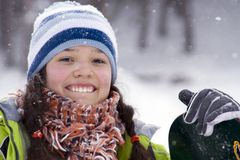 Beautiful girl snowborder. Laughing beautiful girl snowborder, snowfall Royalty Free Stock Photo