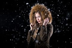 Beautiful girl in a snowfall. Girl in a warm winter jacket posing in snow on a black background Royalty Free Stock Image