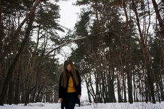 Beautiful girl in a snowy forest. Blonde with long hair. Smiling. In snowing fores Stock Image