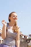 Beautiful girl with soap bubbles. Against a background of sky homes and shooting outdoors Royalty Free Stock Photos