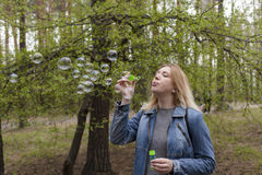 Beautiful girl and soap bubbles. Beautiful girl in spring blow bubbles in the Park area Stock Photography
