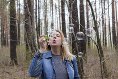 Beautiful girl and soap bubbles. Beautiful girl in spring blow bubbles in the Park area Royalty Free Stock Photos
