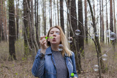 Beautiful girl and soap bubbles. Beautiful girl in spring blow bubbles in the Park area Stock Images