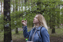 Beautiful girl and soap bubbles. Beautiful girl in spring blow bubbles in the Park area Royalty Free Stock Images