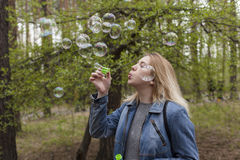 Beautiful girl and soap bubbles. Beautiful girl in spring blow bubbles in the Park area Royalty Free Stock Photography