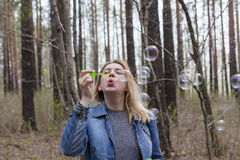 Beautiful girl and soap bubbles. Beautiful girl in spring blow bubbles in the Park area Stock Photo