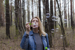 Beautiful girl and soap bubbles. Beautiful girl in spring blow bubbles in the Park area Stock Image