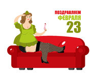 Beautiful girl in soldiers uniform is sitting on red couch. Russ. Ian text: on 23 February. Defenders of Fatherland Day. Military holiday in Russia Royalty Free Stock Photos