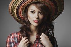 Beautiful girl with sombrero portrait. On grey background stock image
