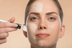 Beautiful girl in spa applying facial cosmetic Royalty Free Stock Photo