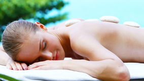 Beautiful girl on spa bed in tropical outdoor stock footage