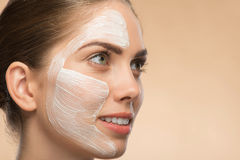 Beautiful girl in spa with cosmetic cream on her Stock Photos