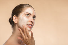 Beautiful girl in spa with cosmetic cream on her Stock Images