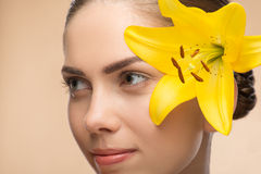 Beautiful girl in spa with flower near her face Stock Photos