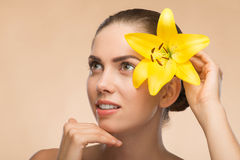 Beautiful girl in spa with flower near her face Royalty Free Stock Images