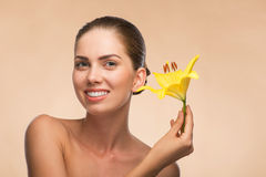 Beautiful girl in spa with flower near her face Royalty Free Stock Photos