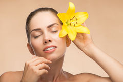 Beautiful girl in spa with flower near her face Stock Images