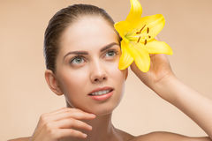 Beautiful girl in spa with flower near her face Royalty Free Stock Image