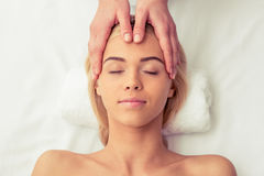 Beautiful girl at spa. Top view of beautiful blonde girl lying with closed eyes at spa while a massage therapist is massaging her head Royalty Free Stock Photography