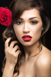 Beautiful girl in the Spanish way of Carmen with red lips and a rose in her hair. Picture taken in the studio on a black background. Beauty face Stock Photography