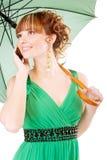 Beautiful girl speaks on phone with green umbrella Stock Image