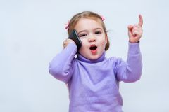 The beautiful girl speaks on the phone and lifted her finger up. The beautiful little girl speaks on the phone and lifted her finger up royalty free stock image