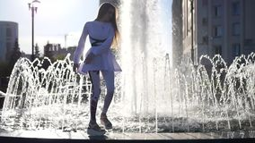 The beautiful girl is spinning standing on the edge of the fountain, and with joy jumps off him. HD, 1920x1080. slow stock video footage