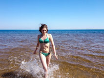 Beautiful girl in splashes of shining water of blue sea Stock Photography