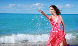 The beautiful girl splashes with water. In red dress Stock Photo