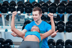 Beautiful girl in sports club with instructor Royalty Free Stock Image