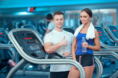 Beautiful girl in sports club with instructor Royalty Free Stock Photo