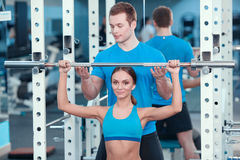 Beautiful girl in sports club with instructor Stock Photography