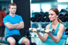 Beautiful girl in sports club with instructor Stock Photos