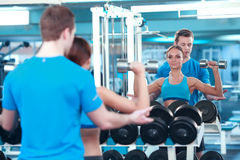 Beautiful girl in sports club with instructor Royalty Free Stock Images