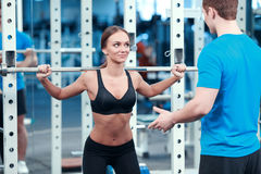 Beautiful girl in sports club with instructor Royalty Free Stock Photography