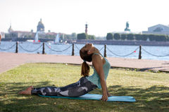 Beautiful girl in a sports-fitting clothes and headphones doing fitness or yoga on the waterfront in St. Petersburg. Royalty Free Stock Photography