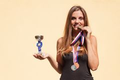 Beautiful girl and sports medals. Sports champion. Awards for sporting achievements. Stock Photos