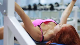 Beautiful girl in sports to a hall carries out exercise with a bar in the gym. Bar Bench Press stock video footage