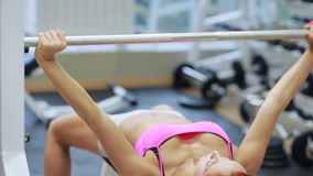 Beautiful girl in sports to a hall carries out exercise with a bar in the gym. Bar Bench Press stock footage