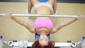 Beautiful girl in sports to a hall carries out exercise with a bar in the gym. Bar Bench Press stock video