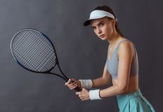 Beautiful tennis player. Beautiful girl in sportswear is holding a tennis racket and looking at camera, on gray background stock images
