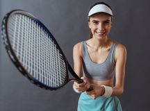 Beautiful tennis player. Beautiful girl in sportswear is holding a tennis racket, looking at camera and smiling, on gray background royalty free stock photography