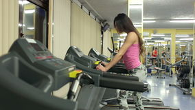 Beautiful girl in sportswear is training on the treadmill. The concept of a healthy lifestyle stock footage