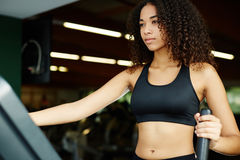Beautiful girl in sportswear using a step machine in fitness center Stock Photos