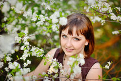 Beautiful girl in spring with blooming trees Royalty Free Stock Image