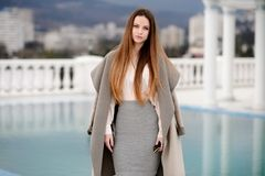 Woman in coat, outdoor. Beautiful girl in spring day outdoors. Girl with long hair stock image