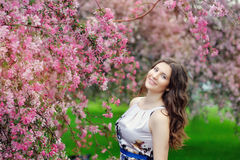 Beautiful girl in spring garden among the blooming trees. With pink flowers Royalty Free Stock Image