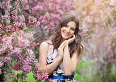Beautiful girl in spring garden among  blooming trees with pink. Beautiful girl in spring garden among blooming trees with pink flowers Royalty Free Stock Image