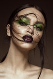 Beautiful girl with spring green makeup and vampire lips. beauty face. Photos shot in studio Stock Image