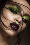 Beautiful girl with spring green makeup and vampire lips. beauty face. Stock Photography